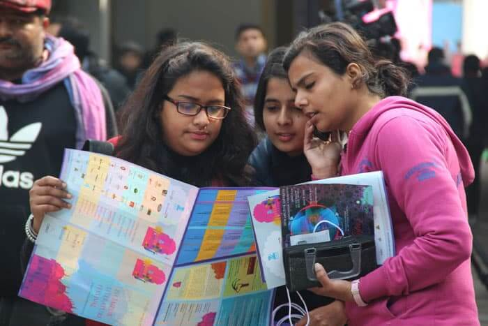 Three girls check their itinerary at the 7th Jaipur Literary festival