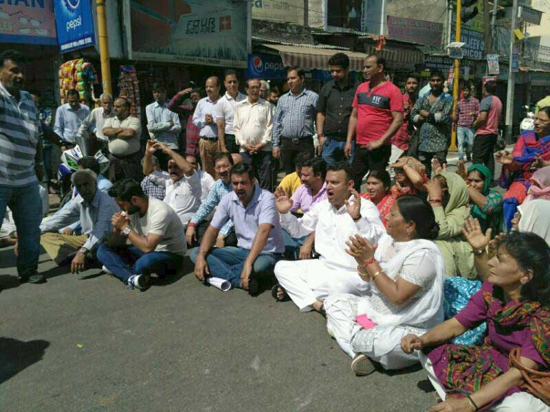 protestors sit in the road at main chowk.