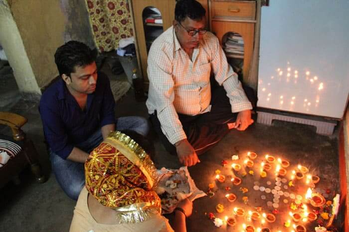 A family performing Puja (prayers) for the Diwali festival. Special prayers are held during the four day festival.