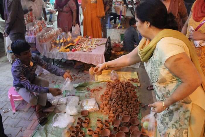 A woman buys clay lamps, named diyas used for the decoration and Puja (prayers), in a market in New Delhi.