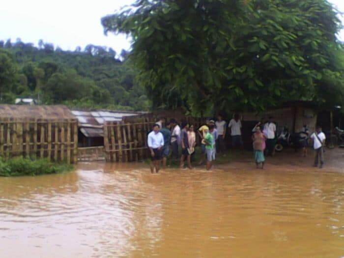 villagers stand in flooded area