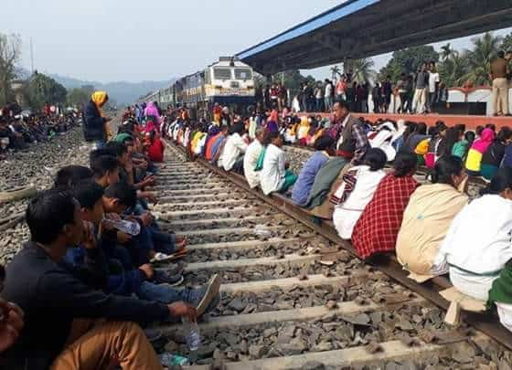 people sit on train line in protest.